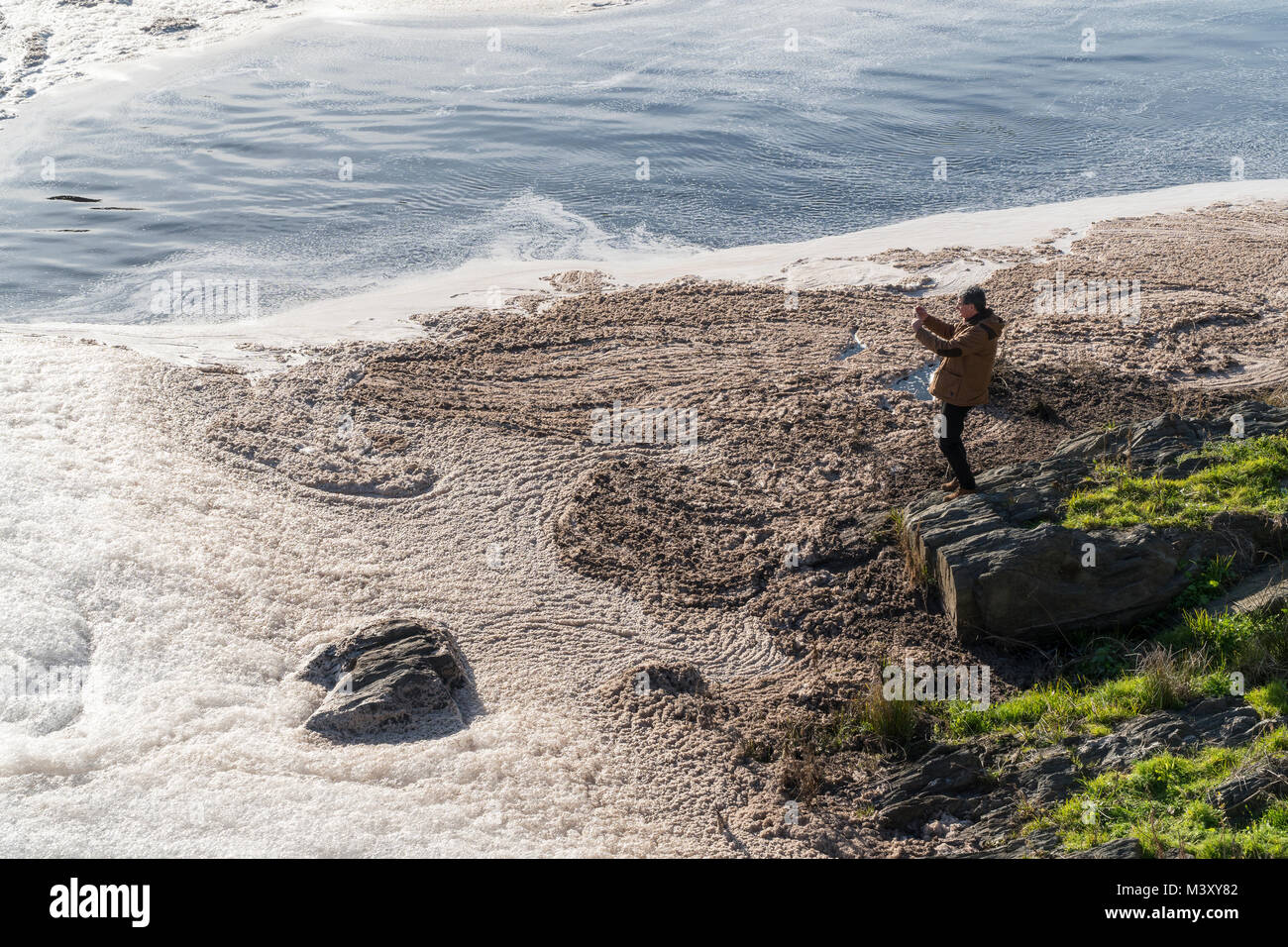 River pollution. Man observing and photographing an ecological accident in the Tagus river caused by paper mills - Stock Image