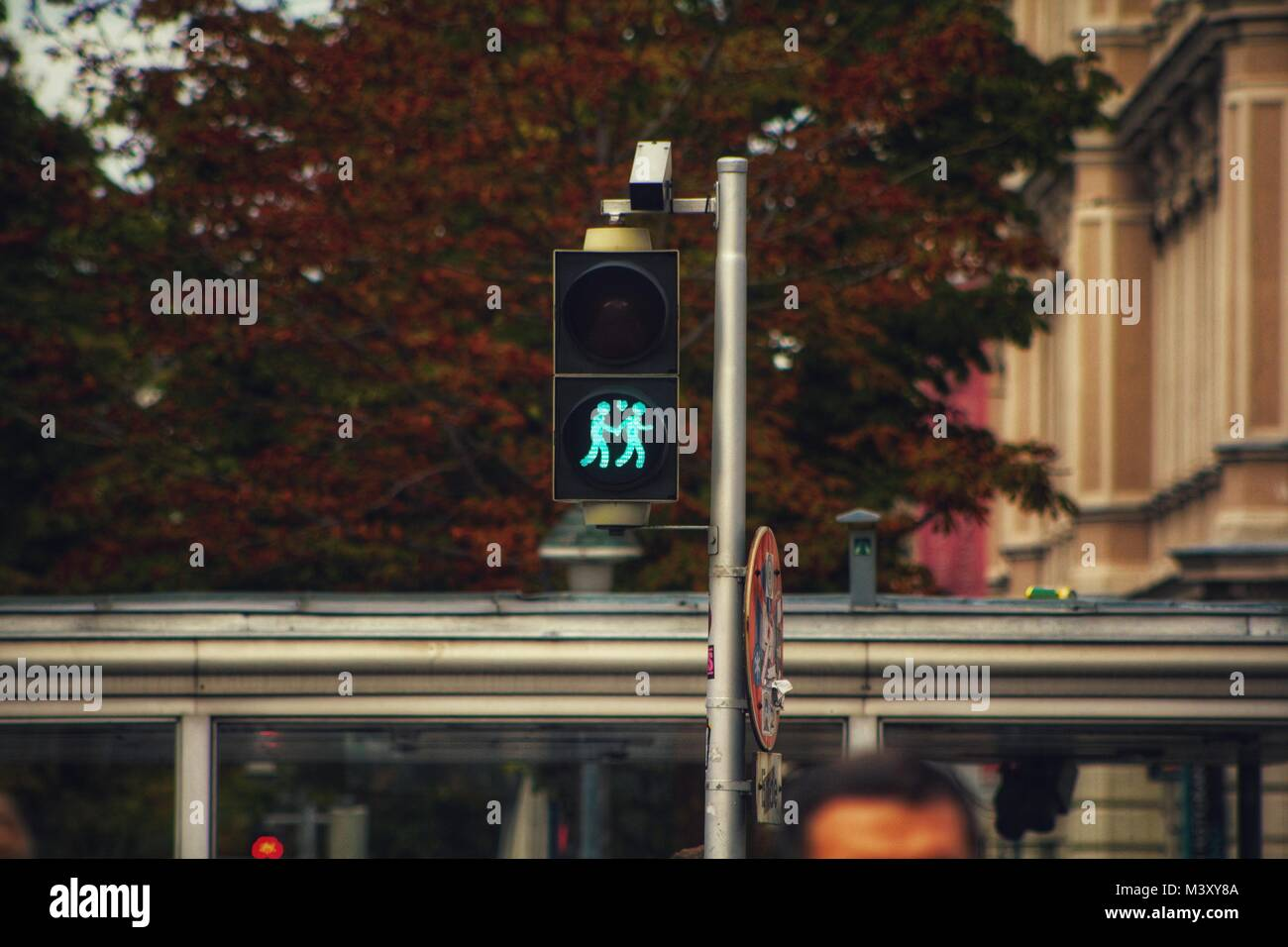 A bright semaphore with a light signal under the banner of the love integration in Vienna, Austria. - Stock Image