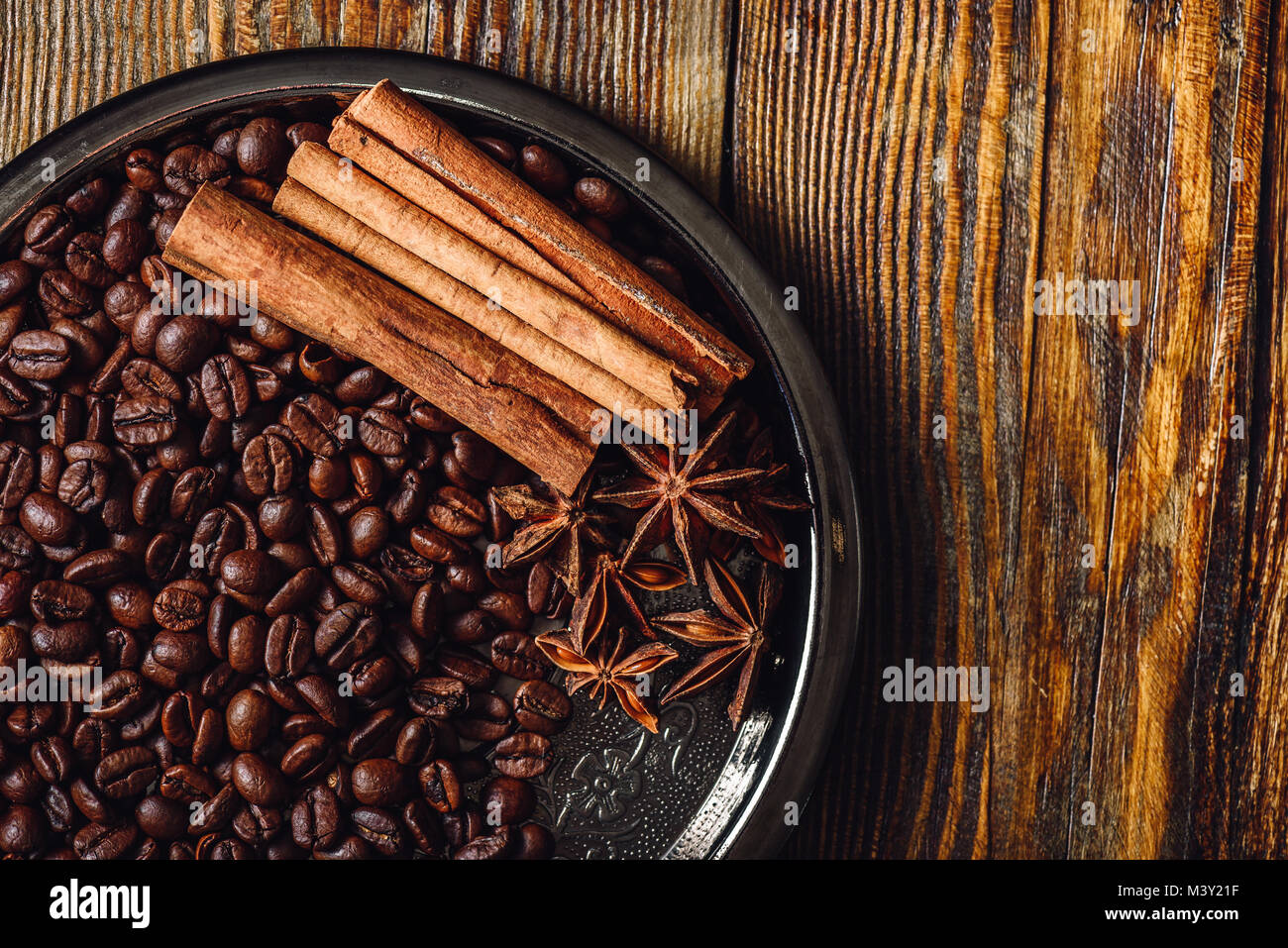 Coffee Beans with Cinnamon Sticks and Chinese Star Anise on Metal Plate. View from Above. Copy Space on the Right - Stock Image
