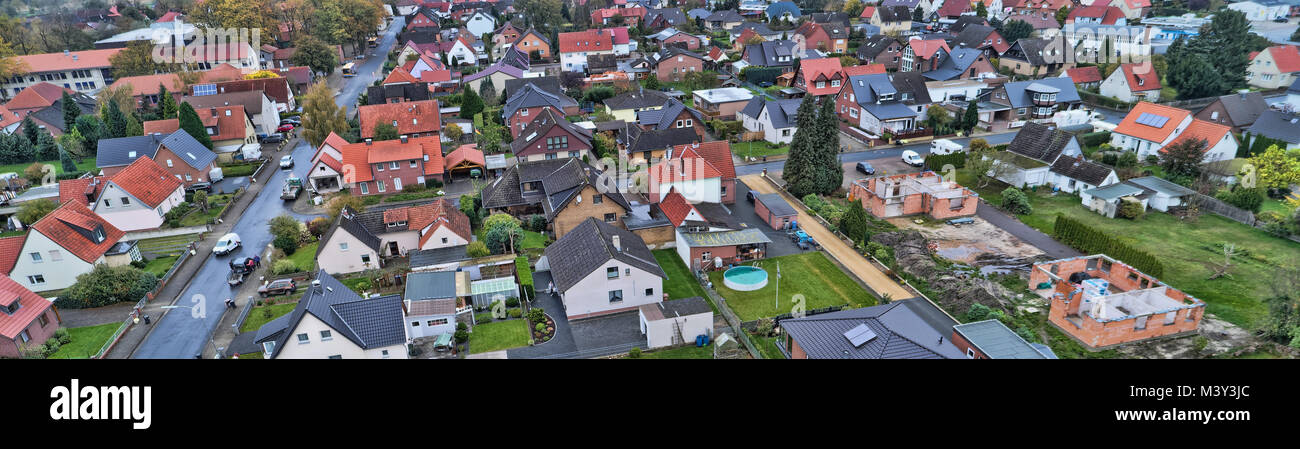 Aerial view of a suburb in Germany with detached houses, streets and gardens. New houses under construction, drone - Stock Image