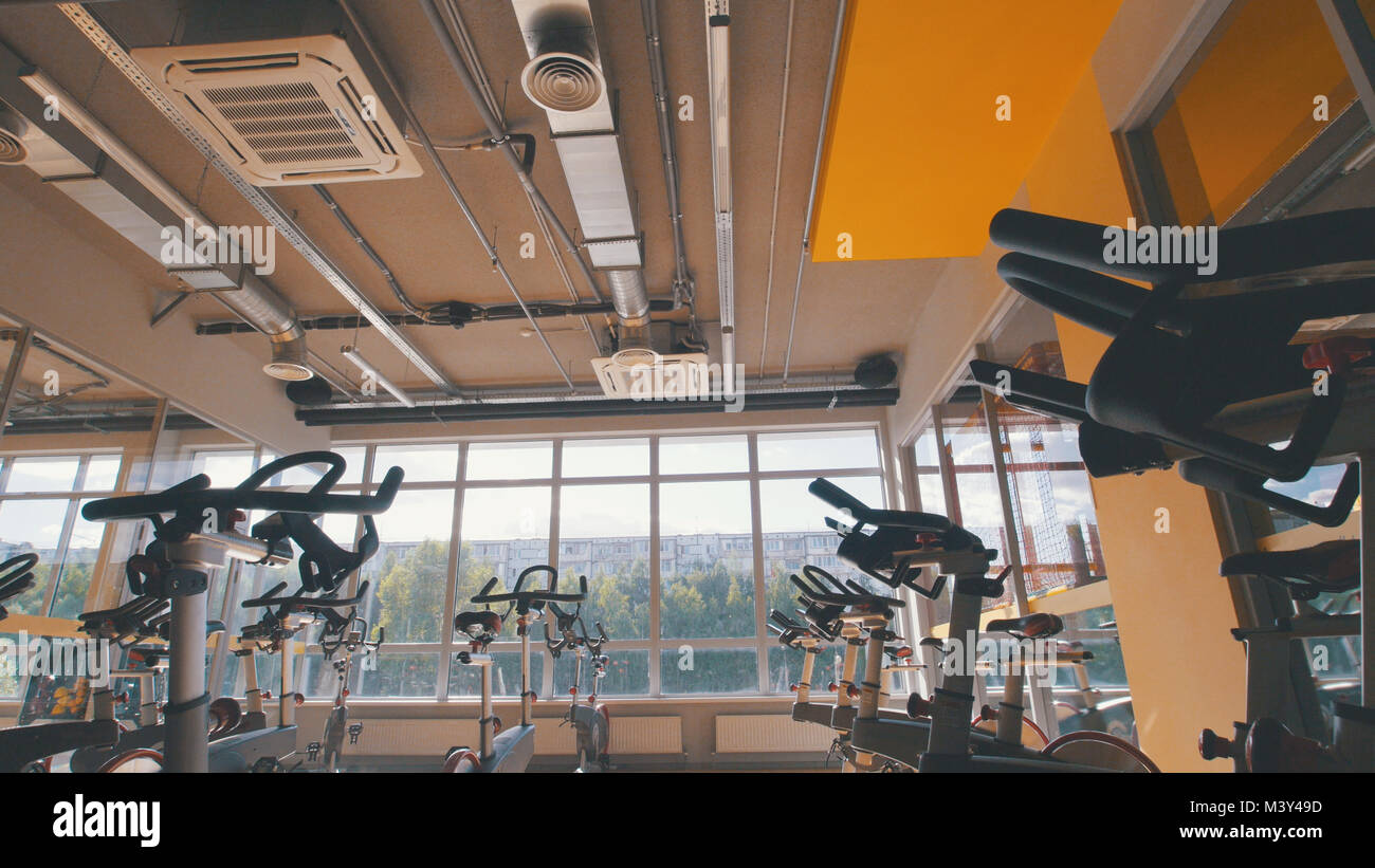 Bicycling simulators in the gym, interior of modern fitness club - Stock Image
