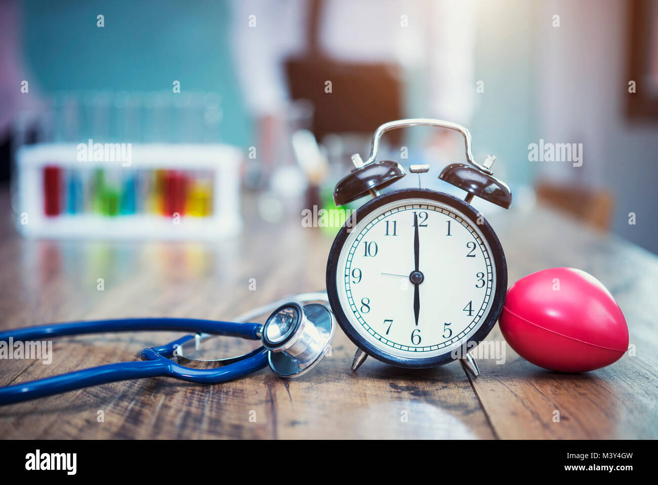 Healthy checking plan concept. Alarm clock with medical instruments stethoscope and red heart on wood table and - Stock Image