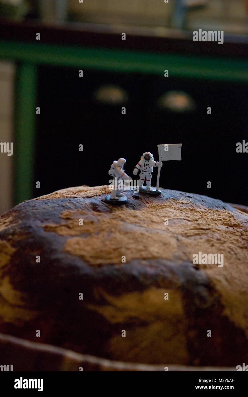 two toy astronaut figures, one with a flag, stand on top of a freshly baked sourdough loaf resembling a moon landing, - Stock Image