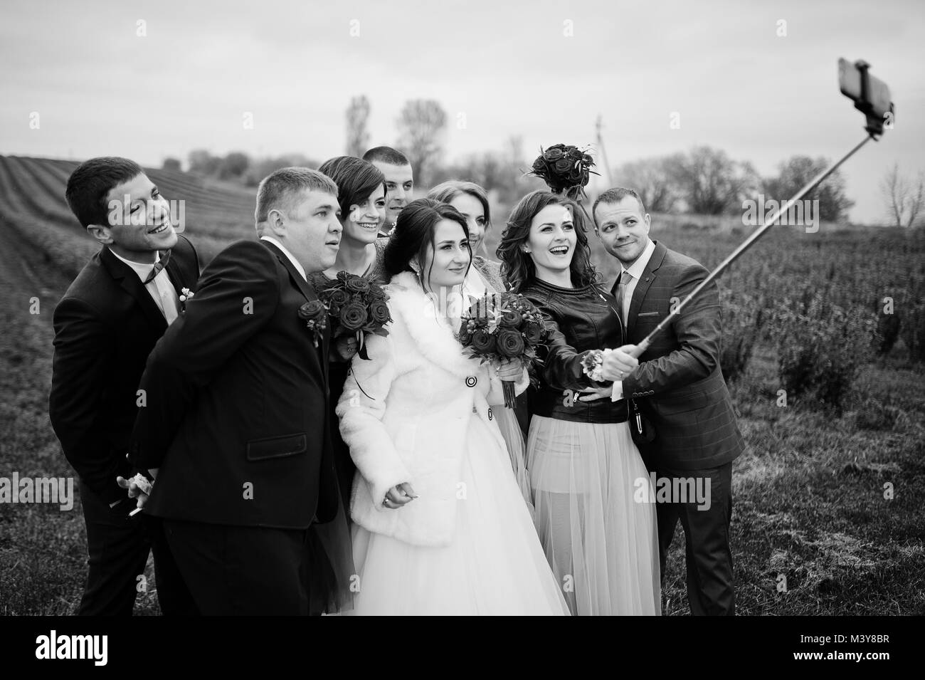 Wedding couple groomsmen and bridesmaids taking selfie in blackcurrant field black and white photo
