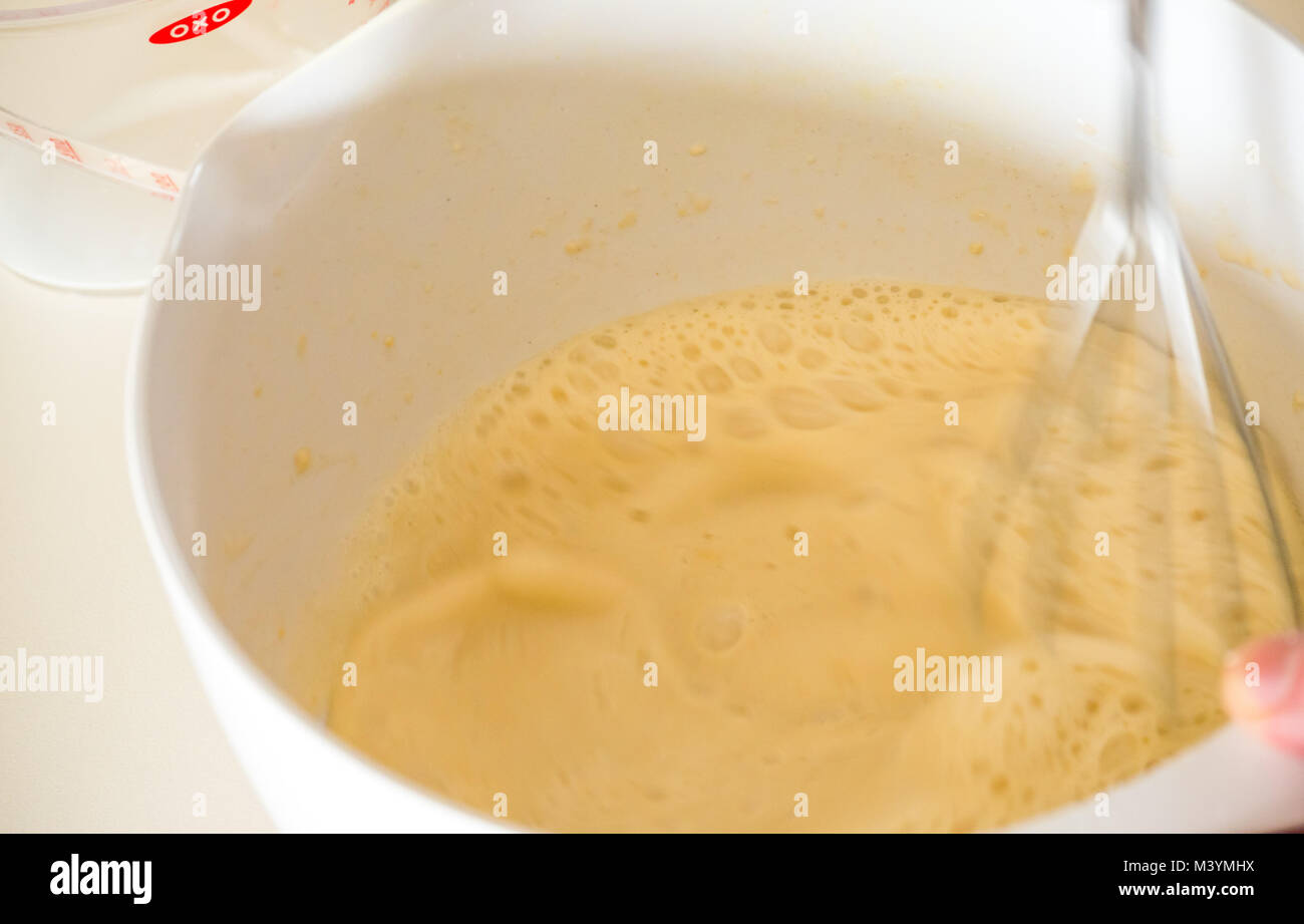 Beating mixture with whisk to make pancake batter for Shrove Tuesday with flour, milk, eggs, and oil in a home kitchen - Stock Image