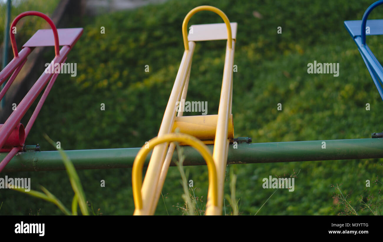 Yellow and red colorful seesaws at a playground. Stock Photo