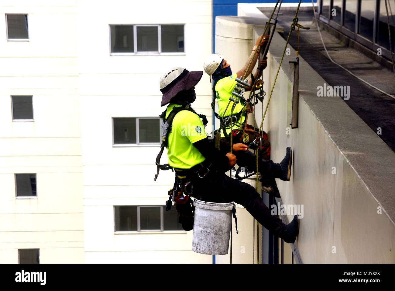 PASIG CITY, PHILIPPINES - FEBRUARY 7, 2018: Professional window cleaners descend down the exterior of a building - Stock Image