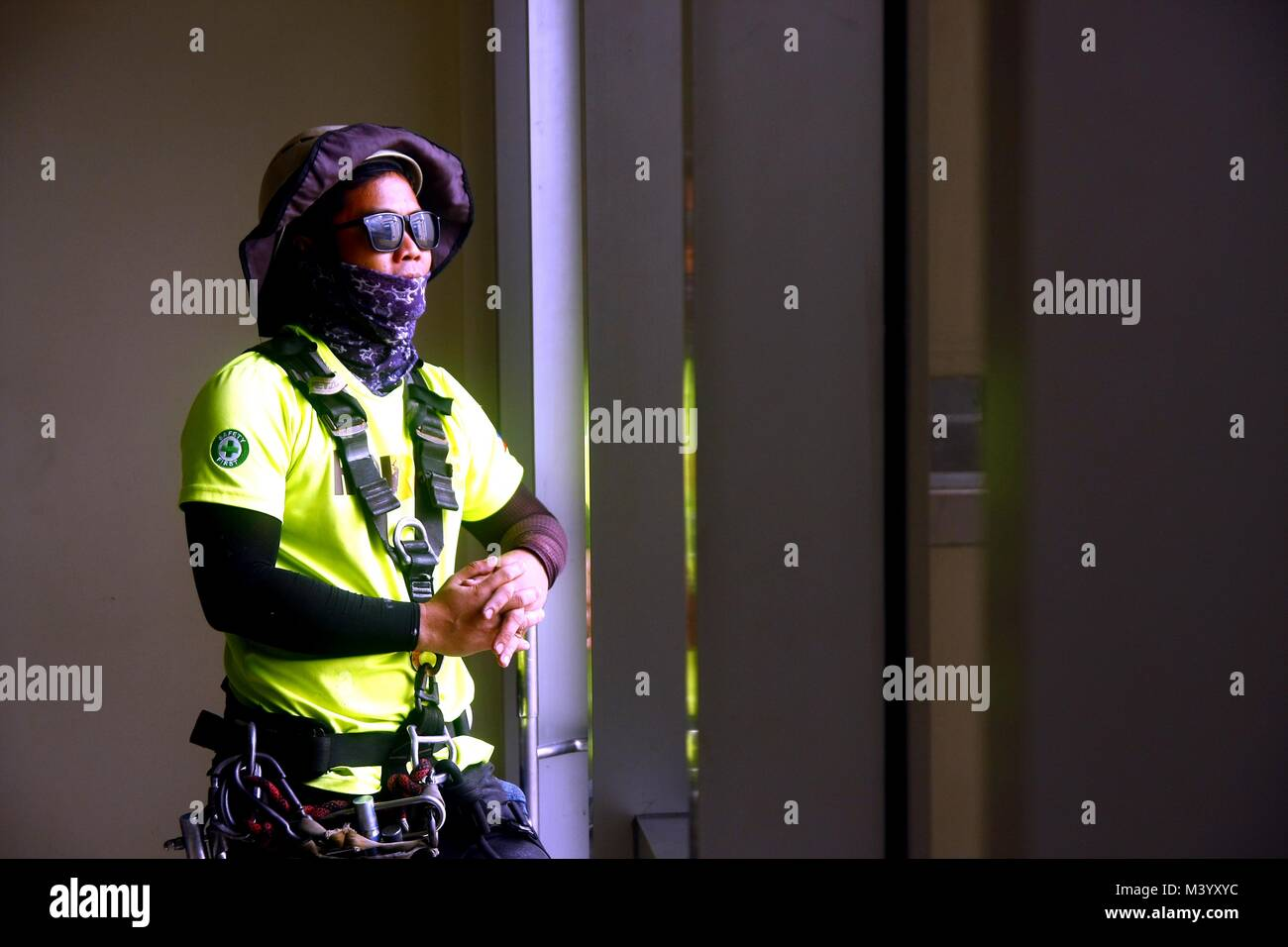 PASIG CITY, PHILIPPINES - FEBRUARY 7, 2018: A professional window cleaner takes a break and looks out the window - Stock Image