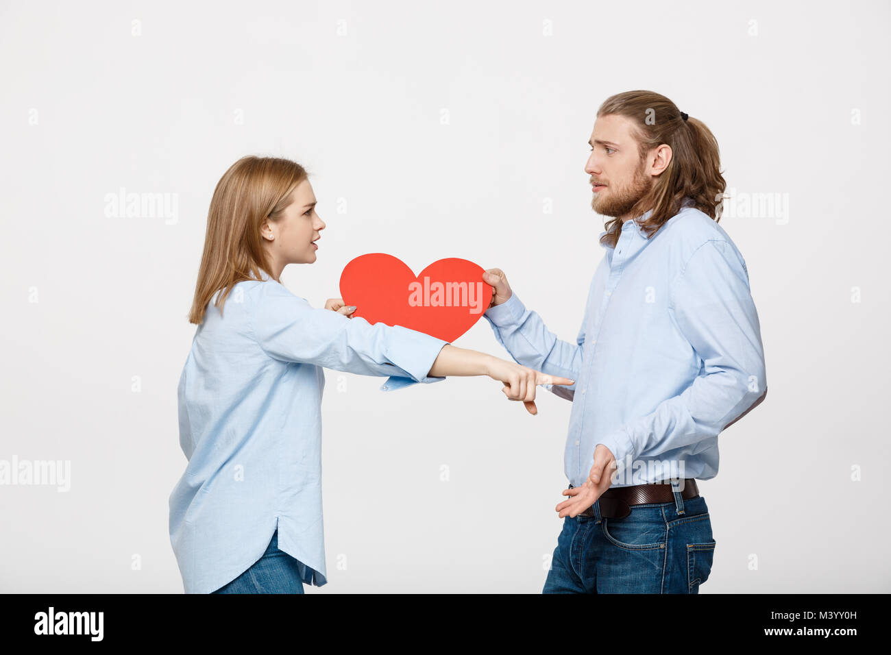 Couple holding heart shape paper with angry facial expression against grey. - Stock Image