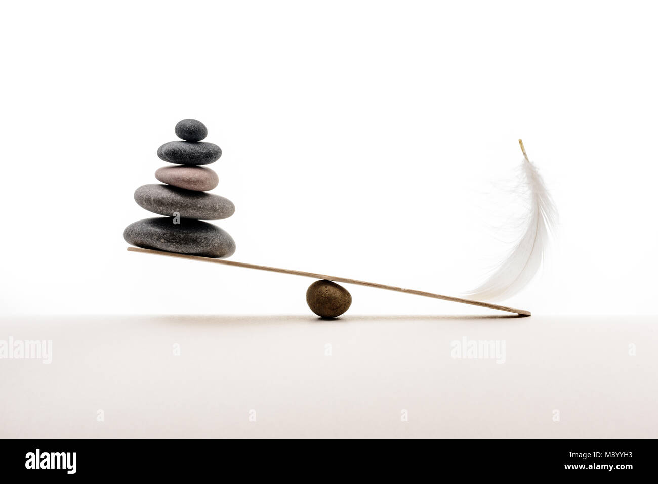 Stone balance with plume. Concept of heavy and light. - Stock Image