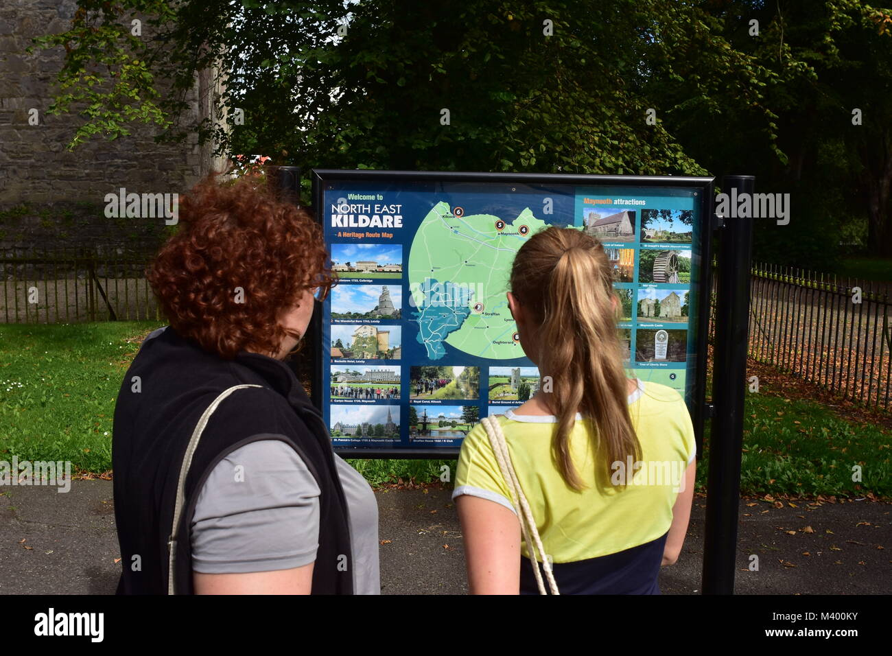 Tourists at heritage route map of North East Kildare in Ireland. - Stock Image