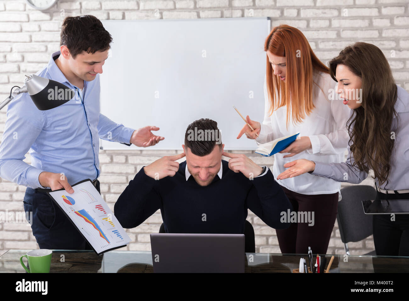 Angry Business People Pointing At Male Colleague During Meeting In Office - Stock Image