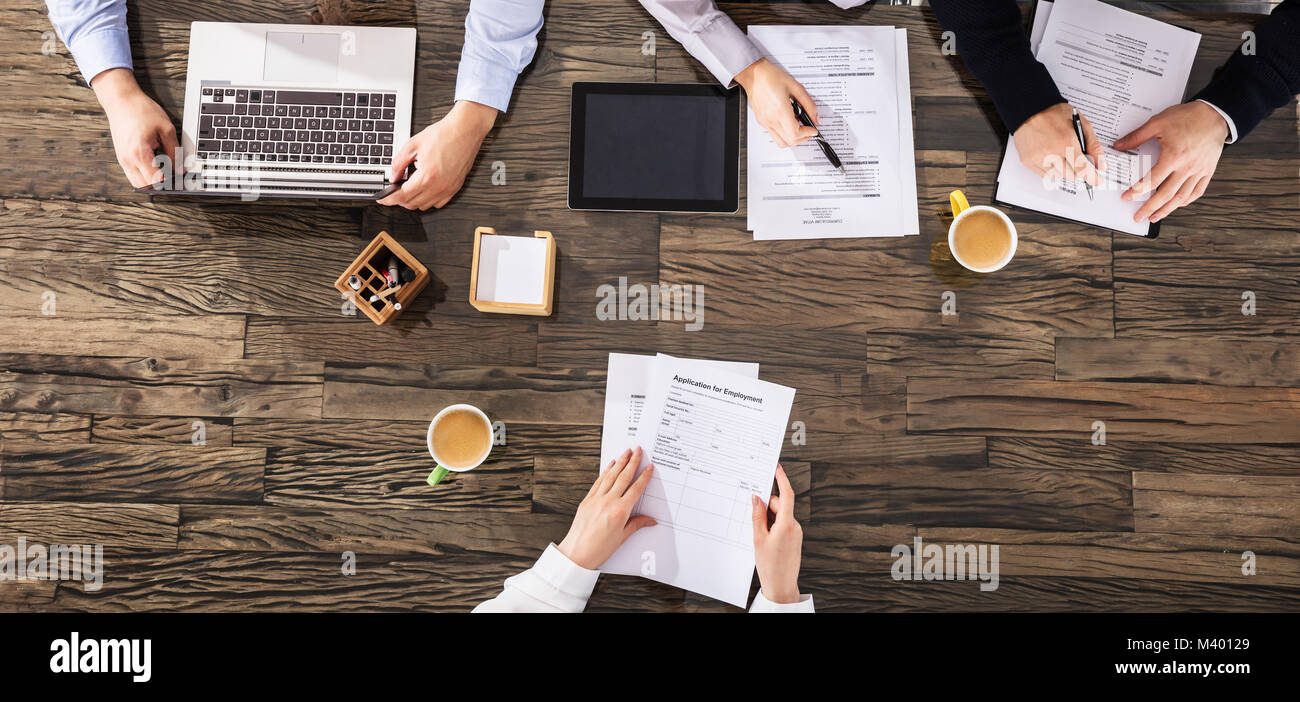 Elevated View Of Businesspeople Taking An Interview Over The Wooden Desk In Office - Stock Image