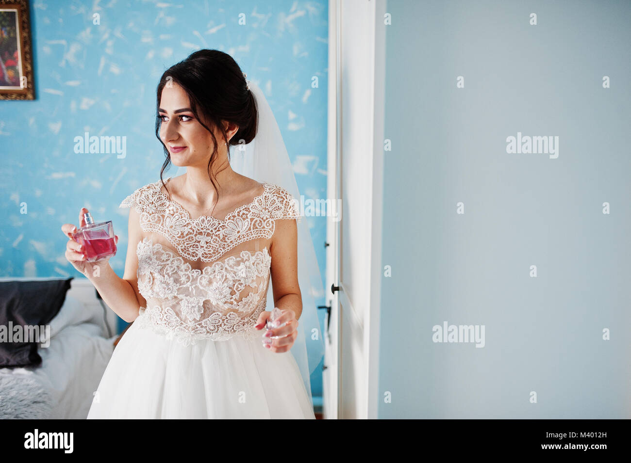 Portrait of a gorgeous bride in her room with perfumes in her hand. Stock Photo