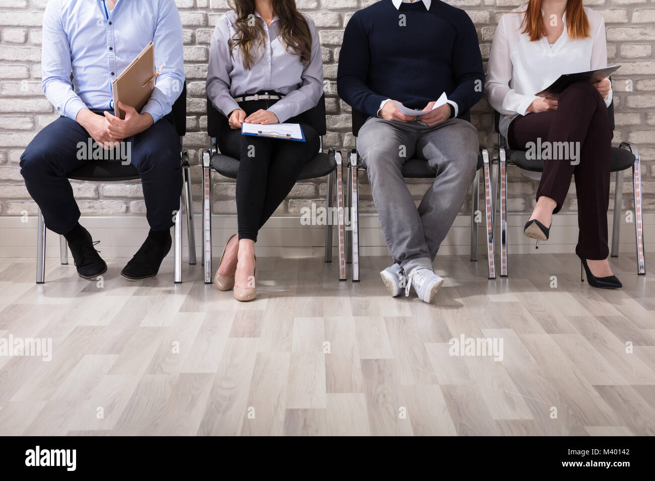 Close-up Of Business People Sitting On Chair Waiting For Job Interview In Office - Stock Image
