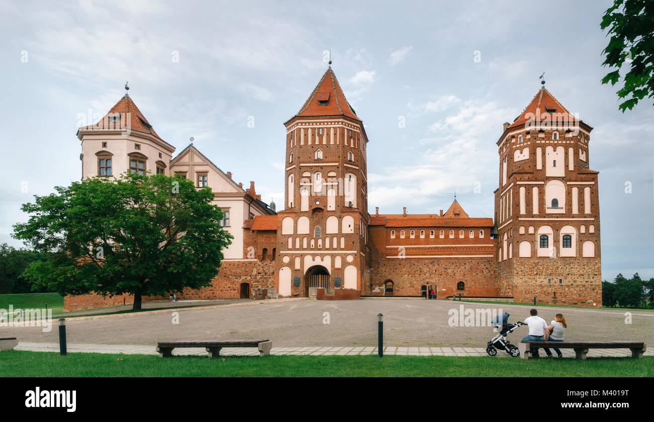 Mir, Belarus - June 25, 2017: Young family with baby sits on bench and admires Medieval castle in Mir, Belarus. - Stock Image