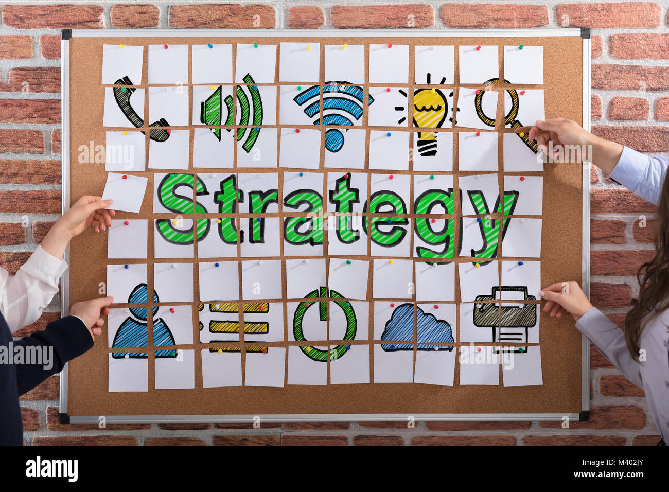 Business People Hands Making Strategy Concept With Adhesive Notes On Corkboard - Stock Image