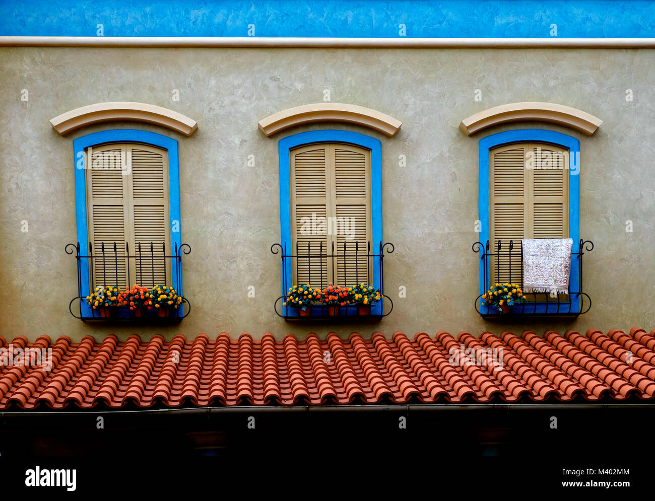 Three shuttered windows with wrought iron window boxes, bright flowers & blue frames. Terracotta orange roof. - Stock Image