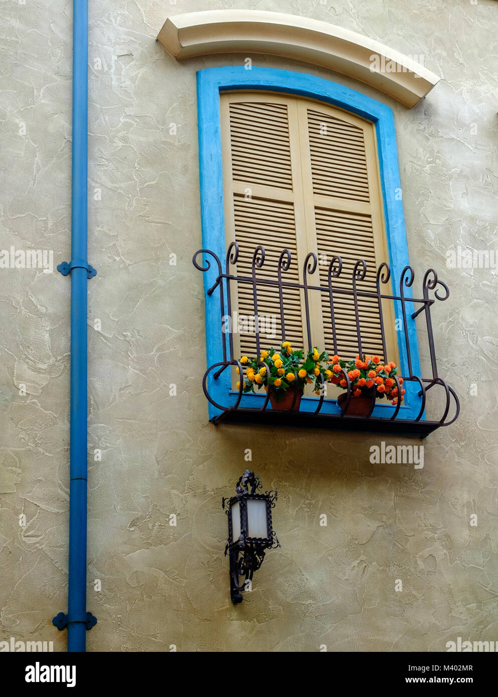Shuttered window with wrought iron window box, bright flowers & blue frame. Blue drain pipe. Retro lamp on building. - Stock Image