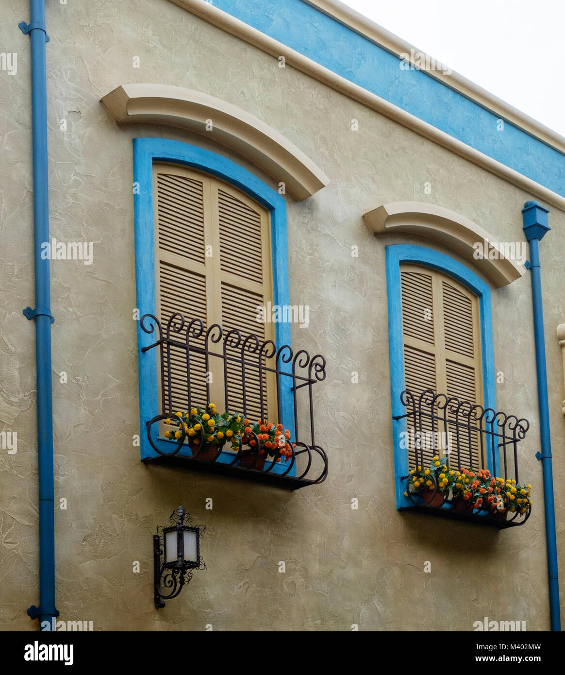 Two shuttered windows with wrought iron window boxes, bright flowers & blue frames. Two blue drain pipes. Retro light on building under one window. Stock Photo