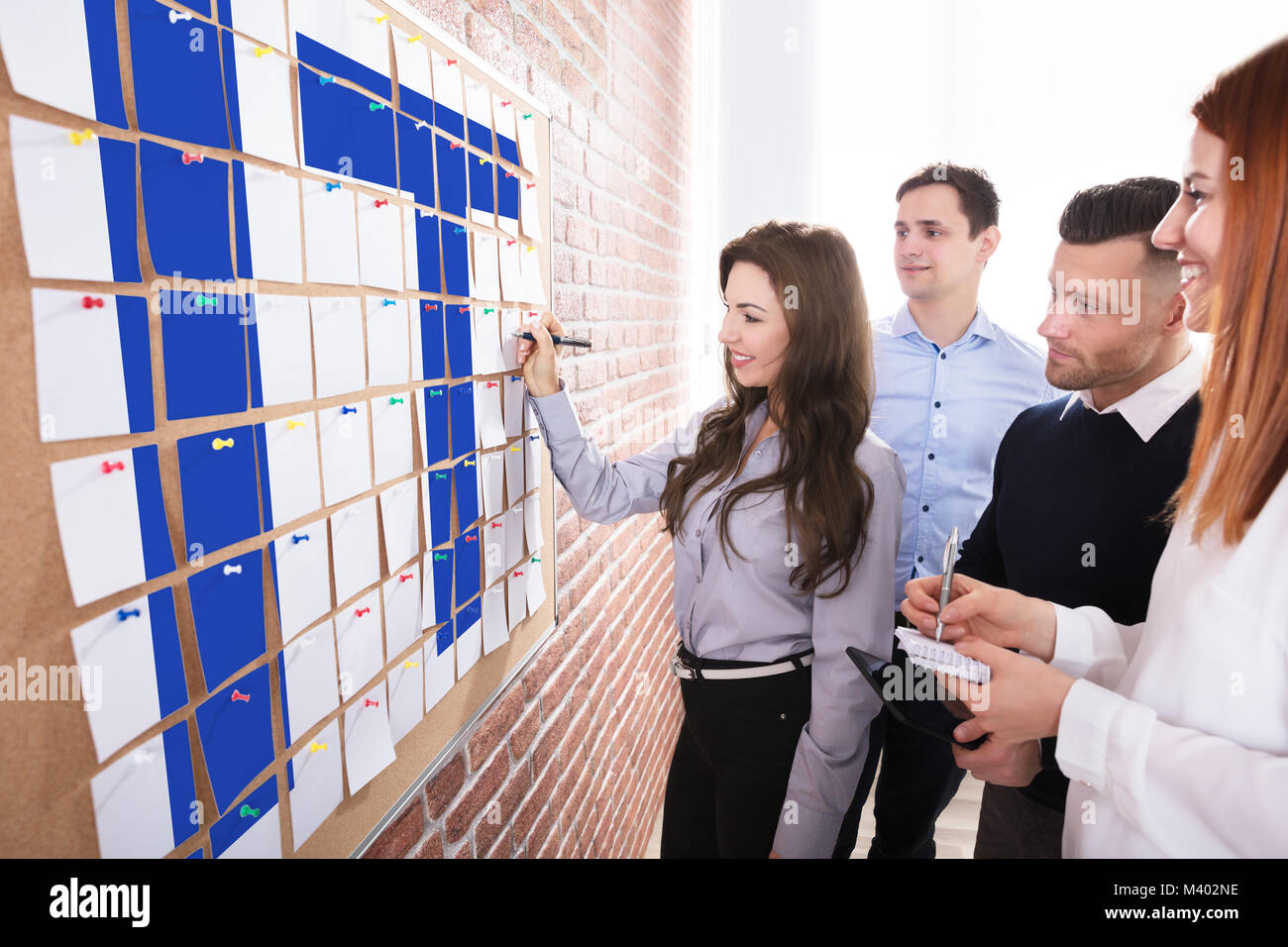 Group Of Business People Planning Information Technology On Adhesive Notes Over The Corkboard