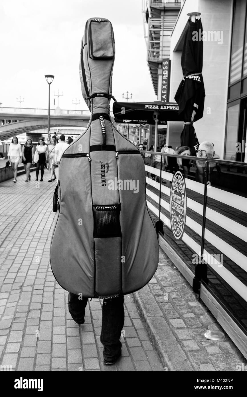 London black and white street photography: Musician walking in street carrying double bass in gig bag on his back. - Stock Image