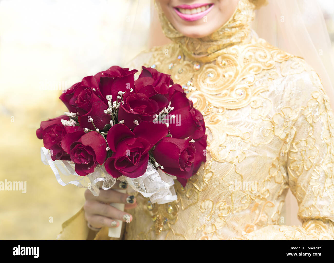 Muslim bride holding a wedding bouquet in her hand, a bunch of red roses flower - Stock Image
