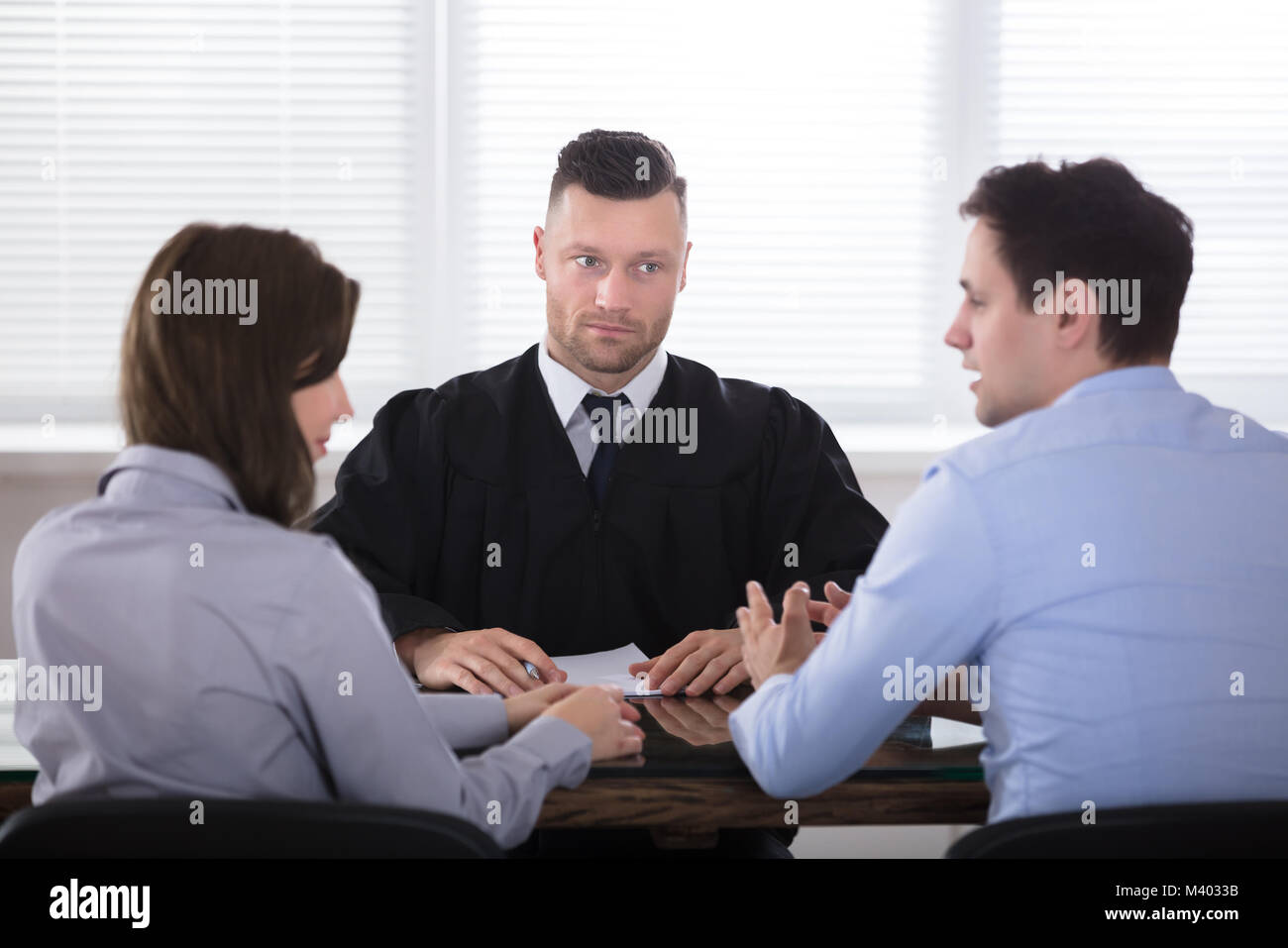 Young Couple Arguing With Each Other In Front Of Judge At Courtroom - Stock Image