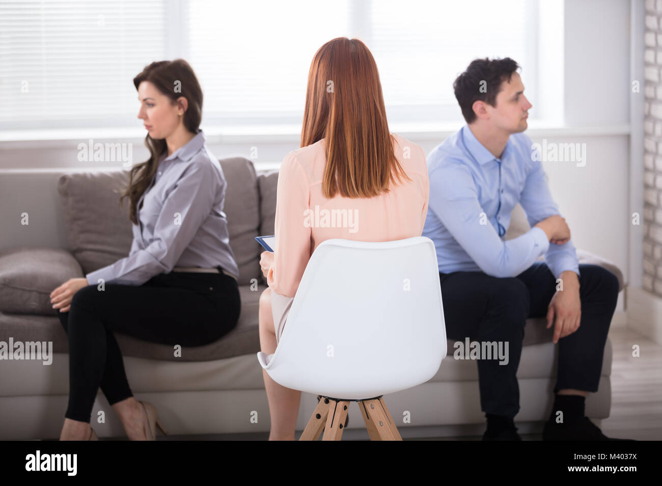 Rear View Of Female Psychologist Sitting With Young Displeased Couple - Stock Image