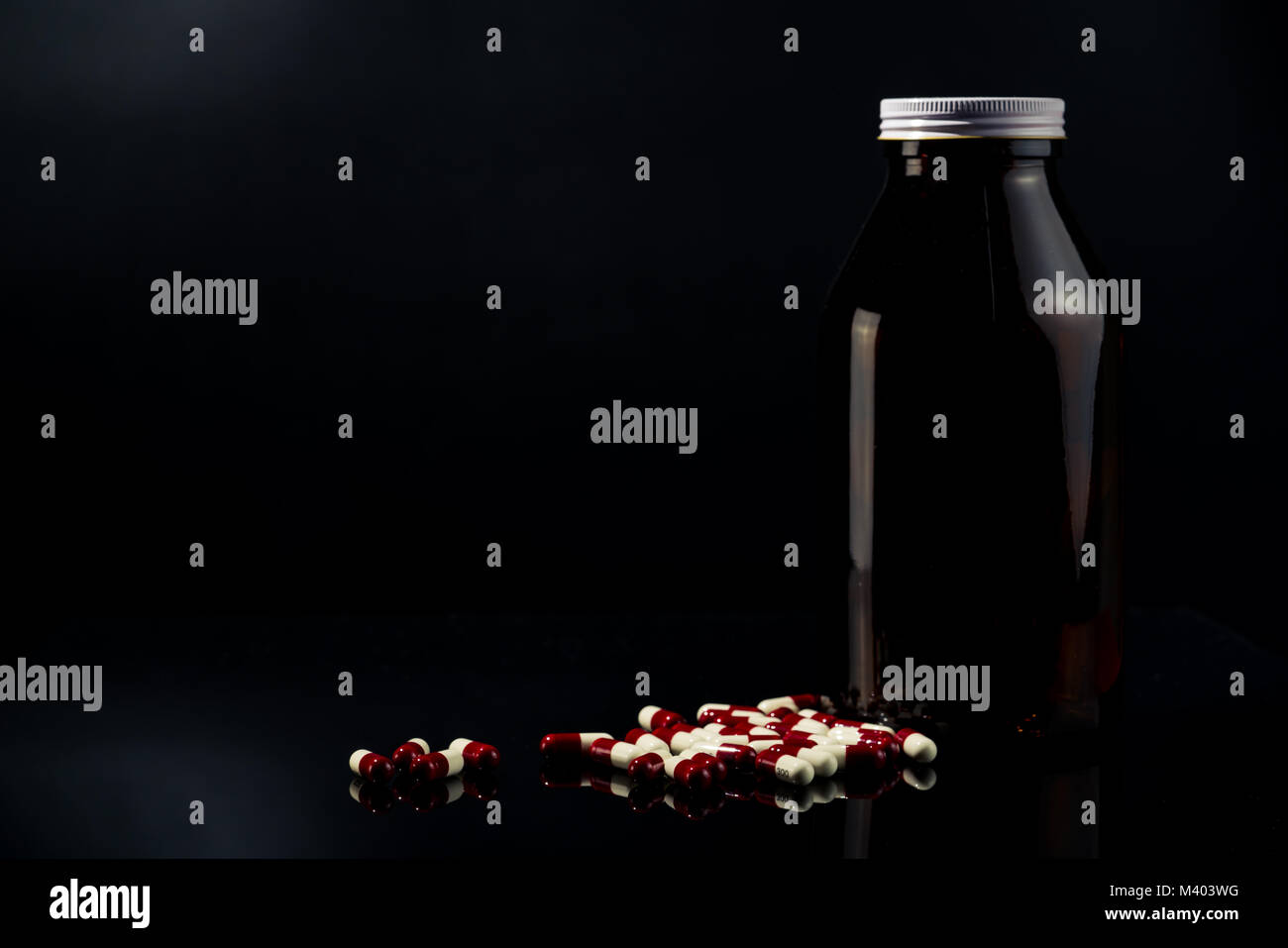 Red, white antimicrobial capsule pills and amber glass bottle on dark background with blank label and copy space Stock Photo
