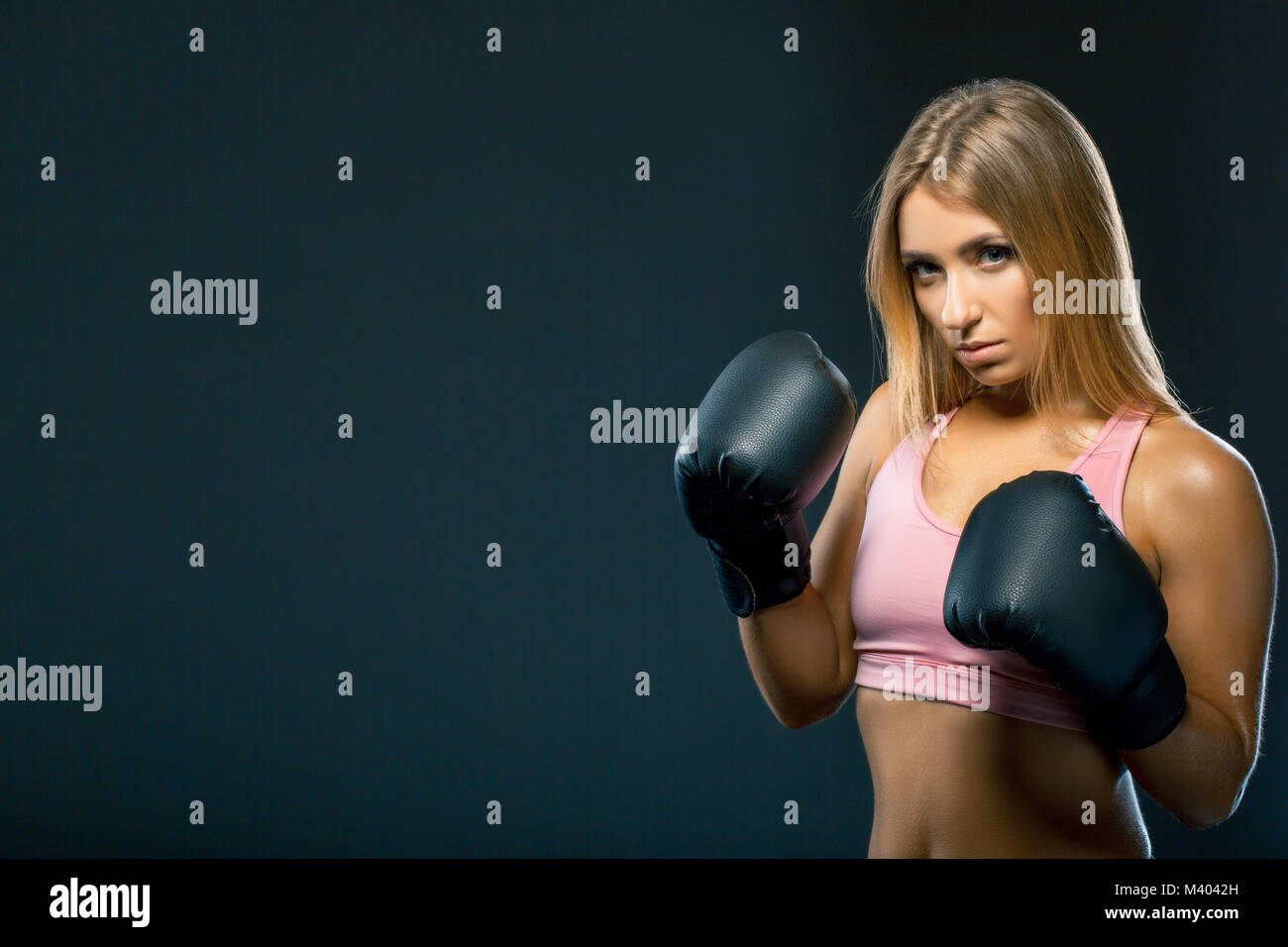 Side view of a gorgeous young woman in pink tank top is wearing large boxing gloves and standing on dark background. - Stock Image