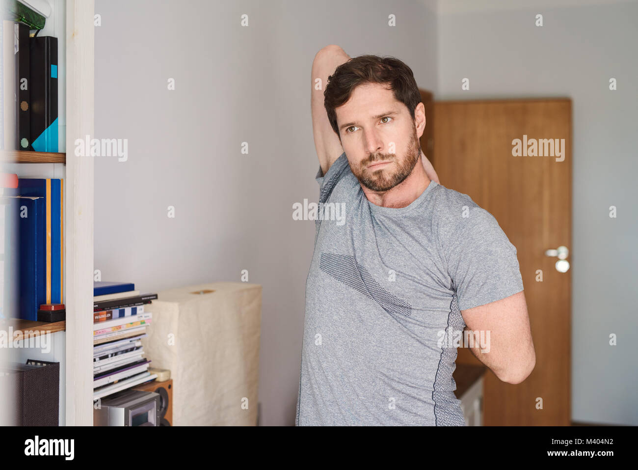 Young man in sportswear stretching before working out at home - Stock Image