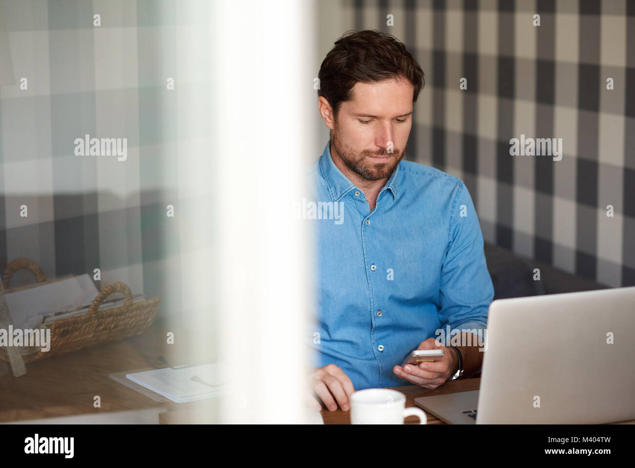 Young man reading text messages while working online from home - Stock Image