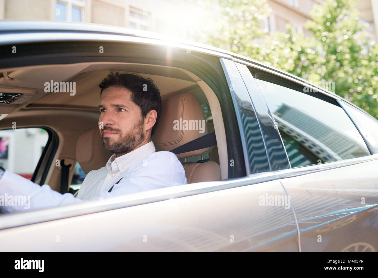 Young man driving his car through city streets - Stock Image