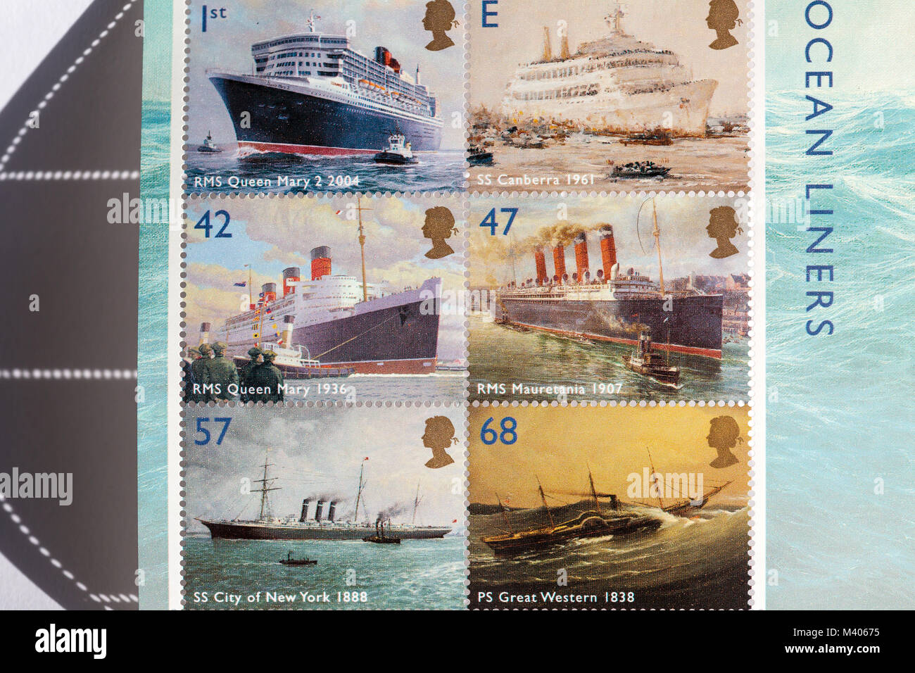 old UK postage stamps showing old and new ocean liners - Stock Image