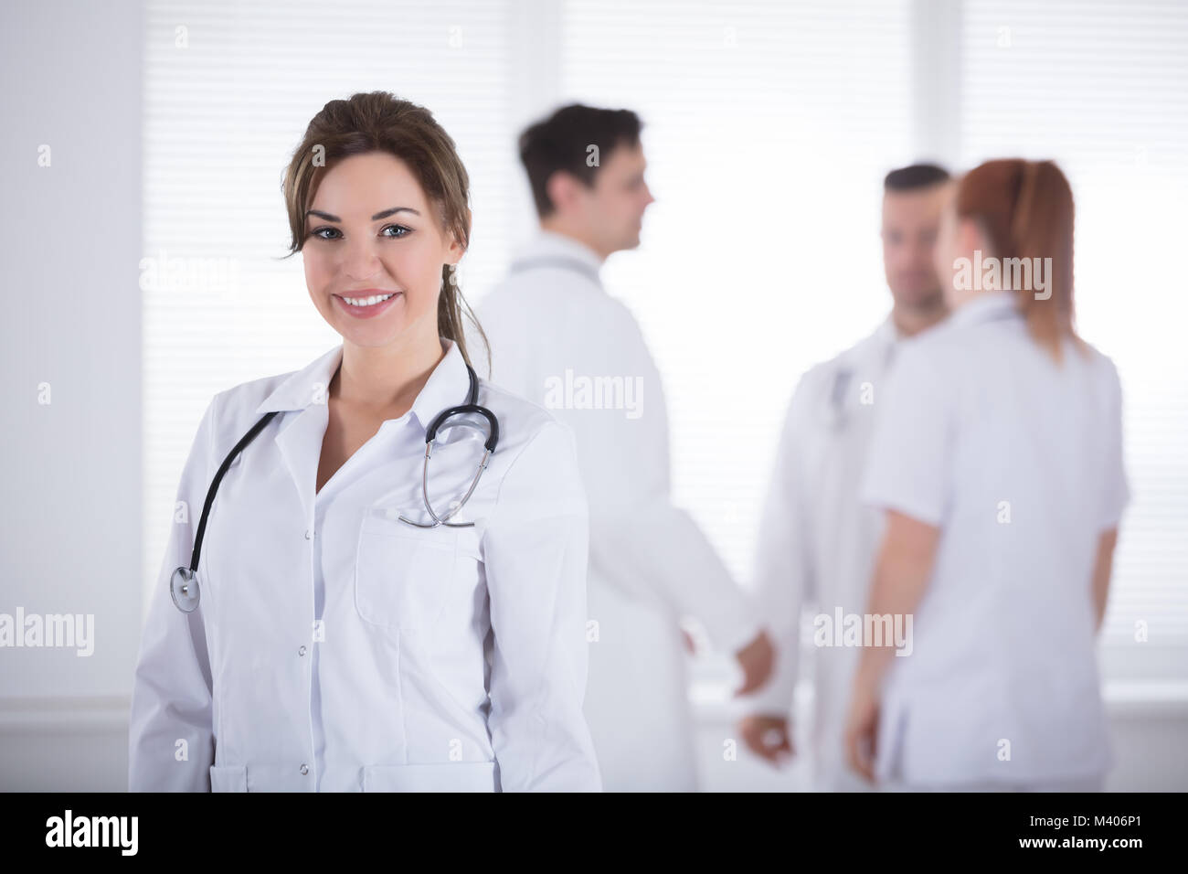 Portrait Of Young Smiling Professional Female Doctor With Stethoscope - Stock Image