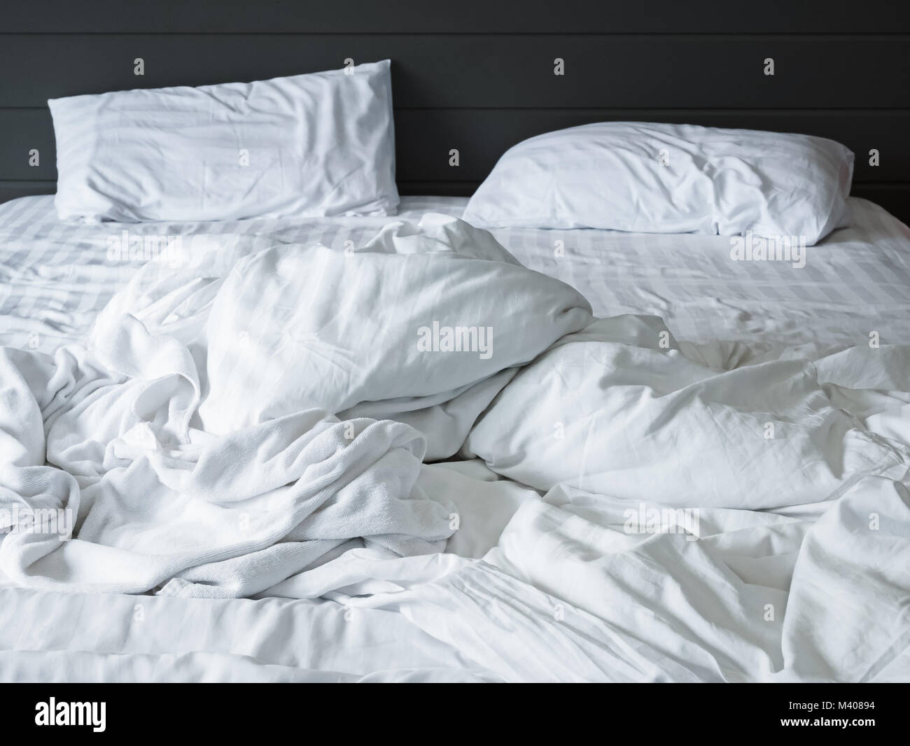 messy white bedding sheets and pillow in bedroom background ,Unmade messy bed after comfort sleep concept - Stock Image