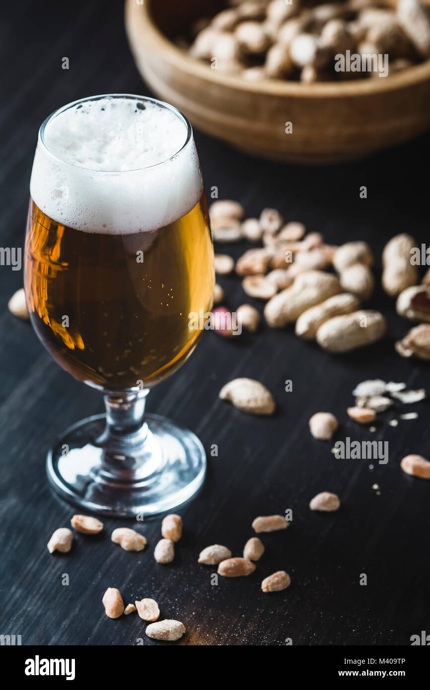 Glass of beer and peanuts on the dark wooden background Stock Photo