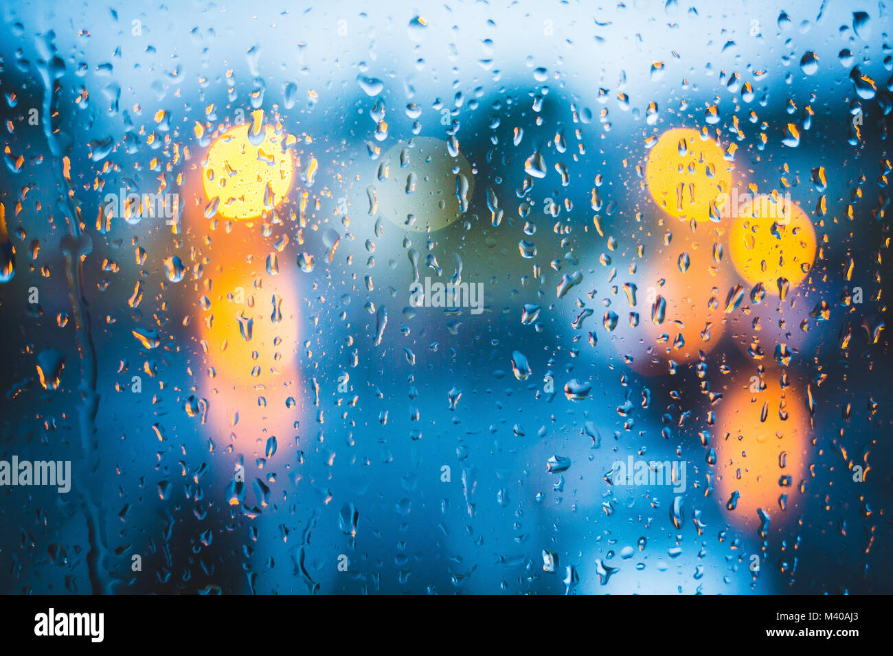 Rain drops on window. Peaceful evening or night at home when raining outside. Water drops on glass. Surface of wet - Stock Image