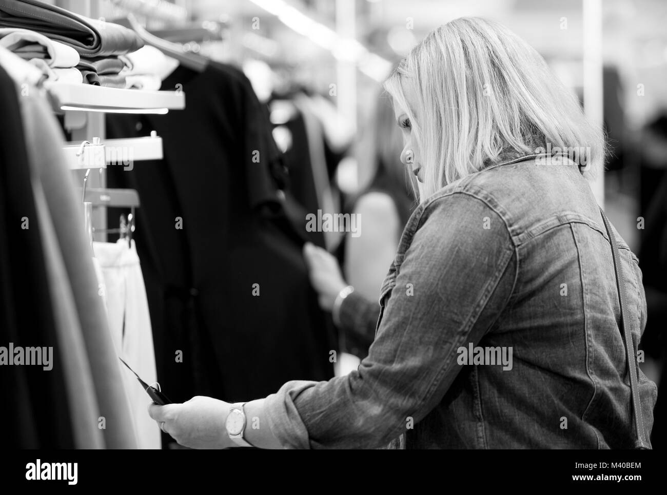 A female shopper examines a tag on an item of clothing in a retail store. - Stock Image