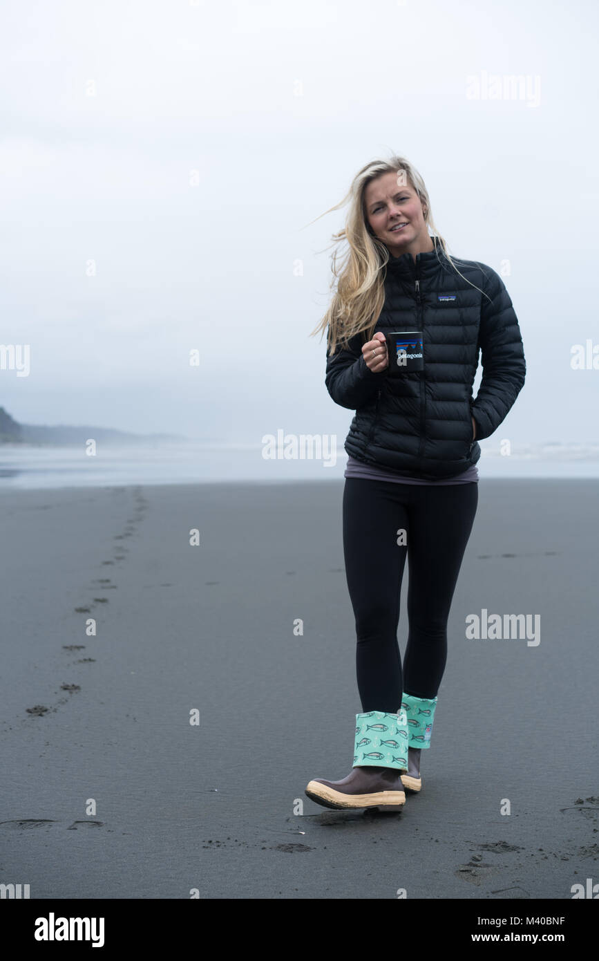 A blonde woman walks along the Oregon coast with a Patagonia coffee mug and jacket, and xtra tough boots designed - Stock Image
