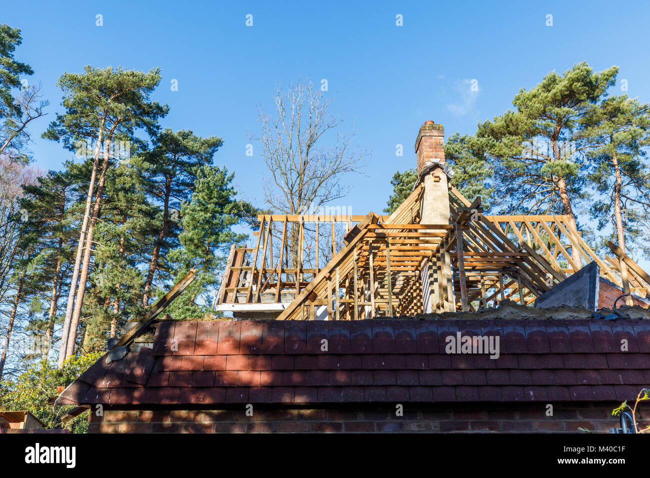 Real estate: skeleton top section of property in the course of demolition for residential redevelopment with exposed - Stock Image