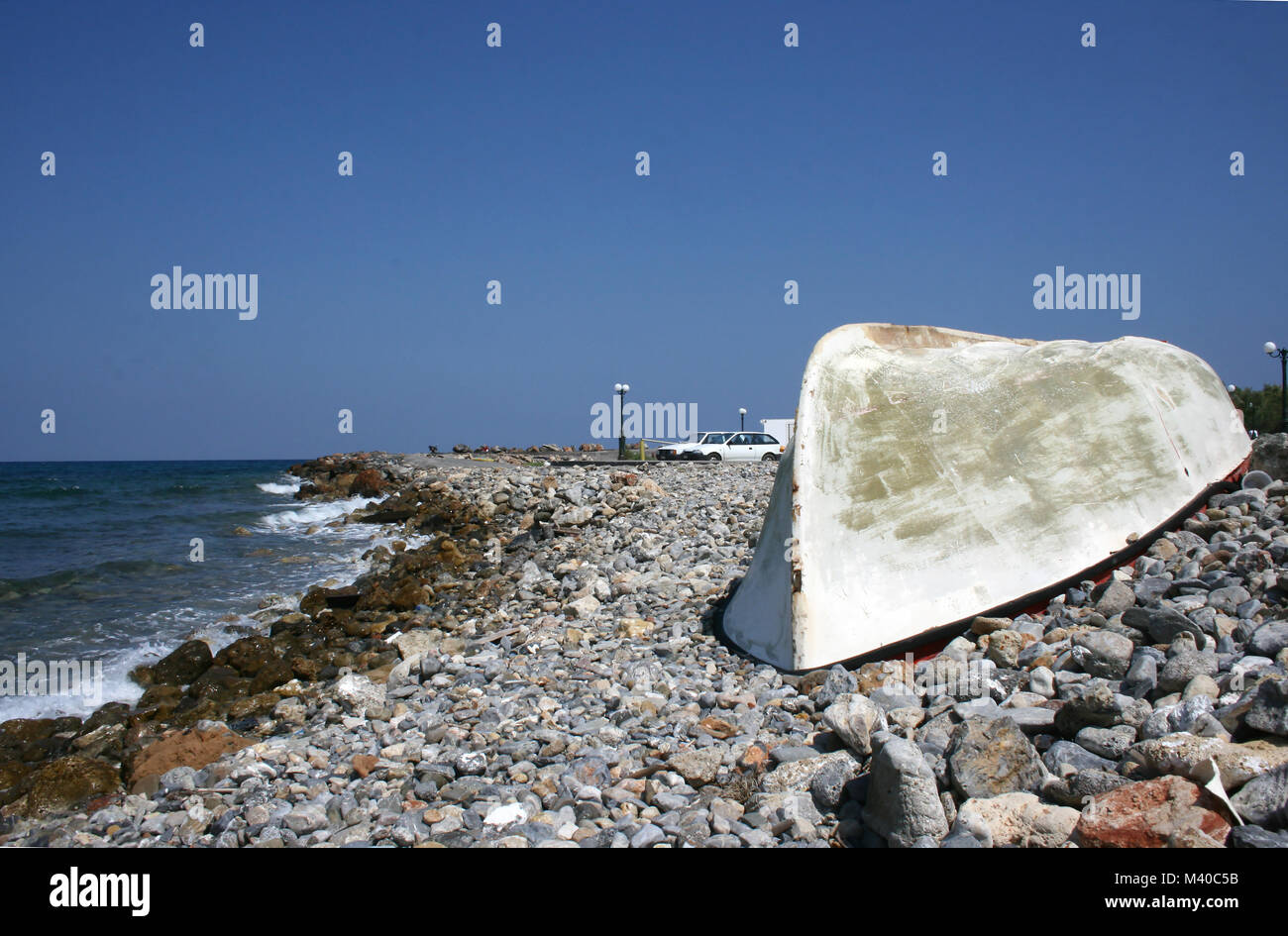 An upturned fishing boat of fibreglass construction on a pebble beach in Southern Crete - Stock Image
