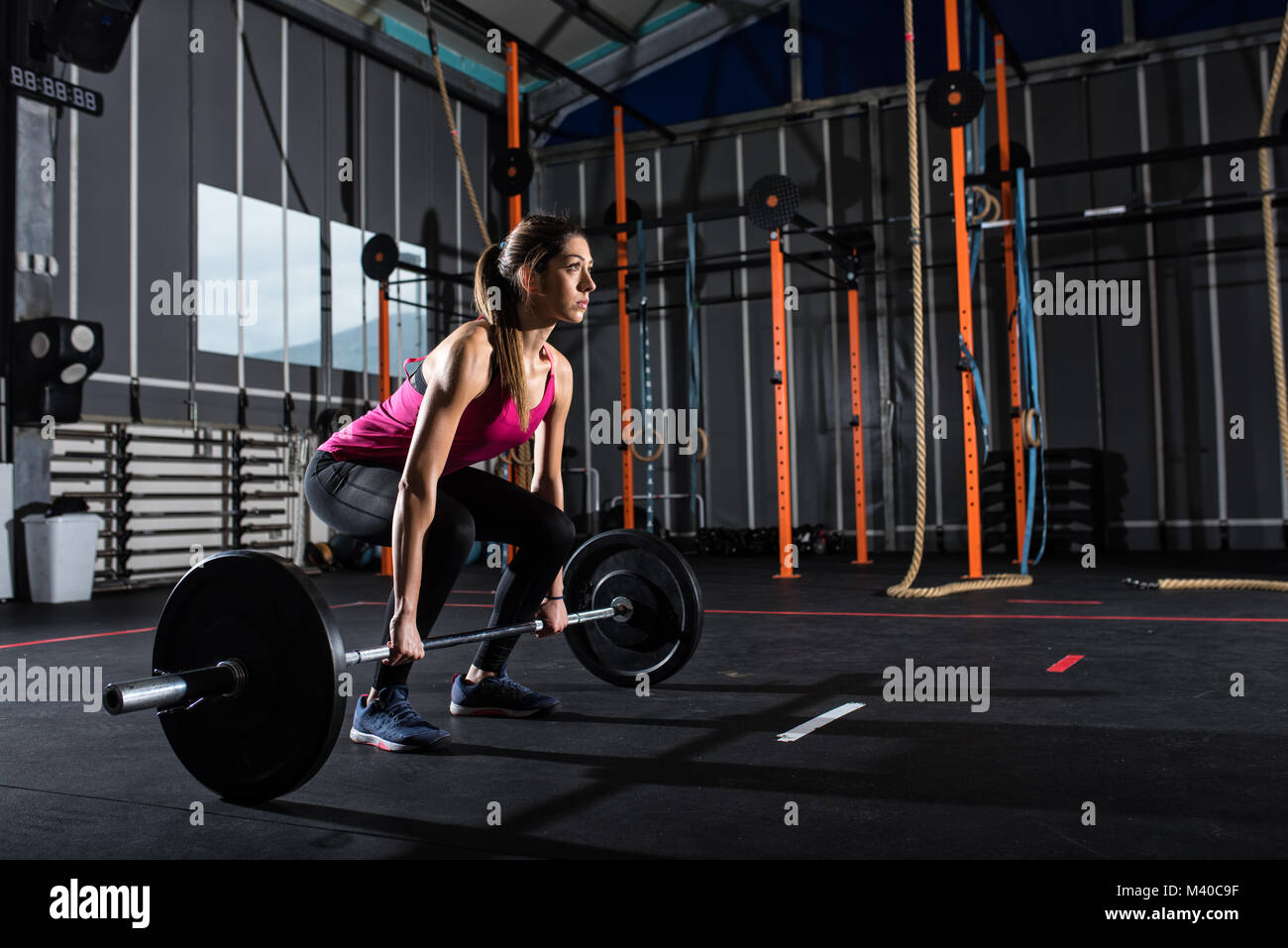 Athletic girl works out at the gym with a barbell - Stock Image