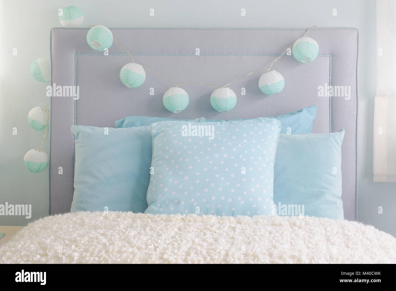 Light Blue Pillows Setting On Bed With Decorative Ball On Headboard Stock Photo Alamy