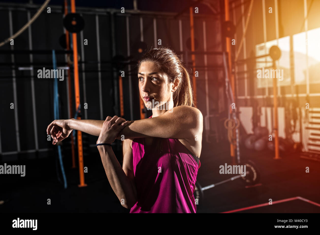 Athletic girl does stretching exercises at the gym Stock Photo