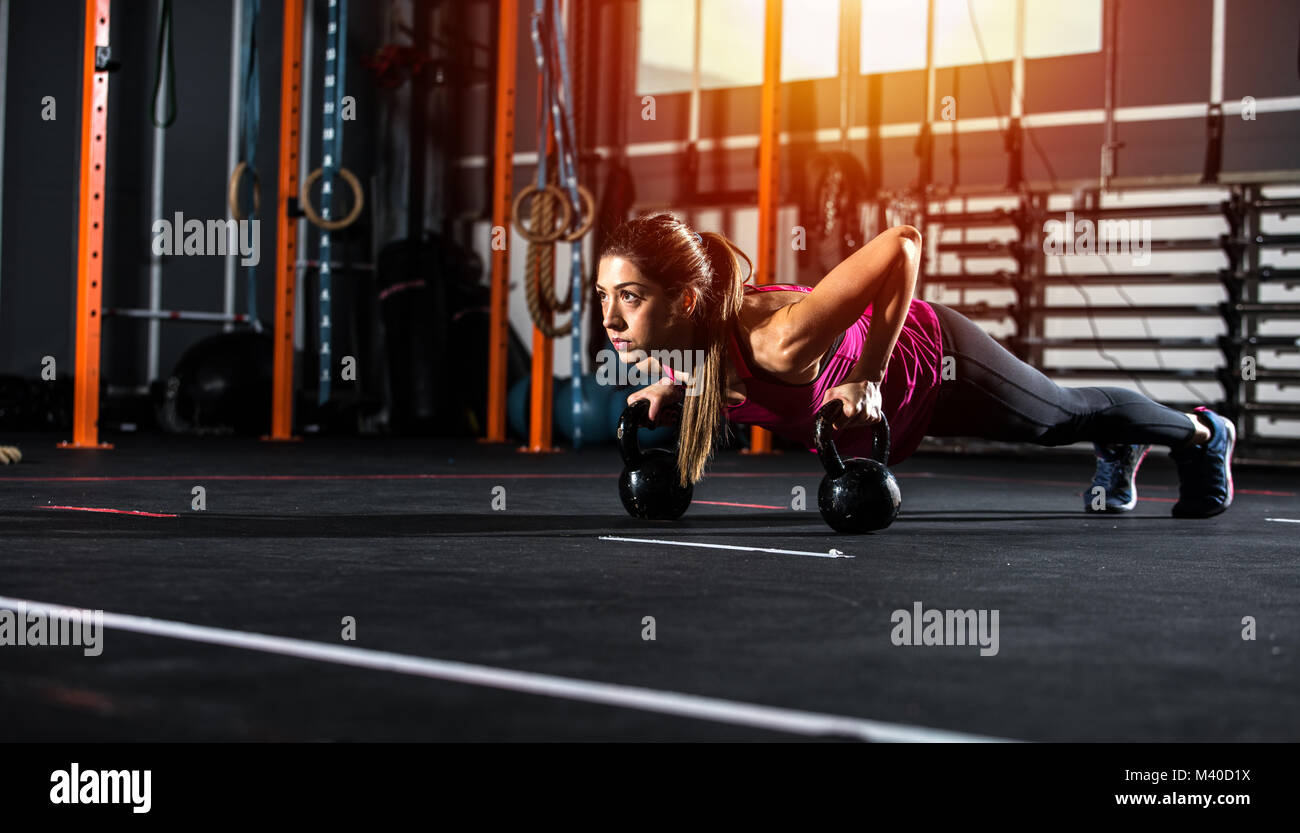 Athletic girl works out at the gym with a kettlebell - Stock Image