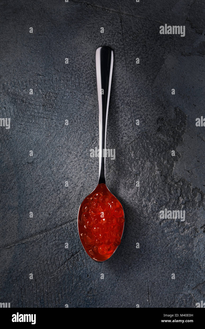 Spoon of red caviar on the table, top view - Stock Image