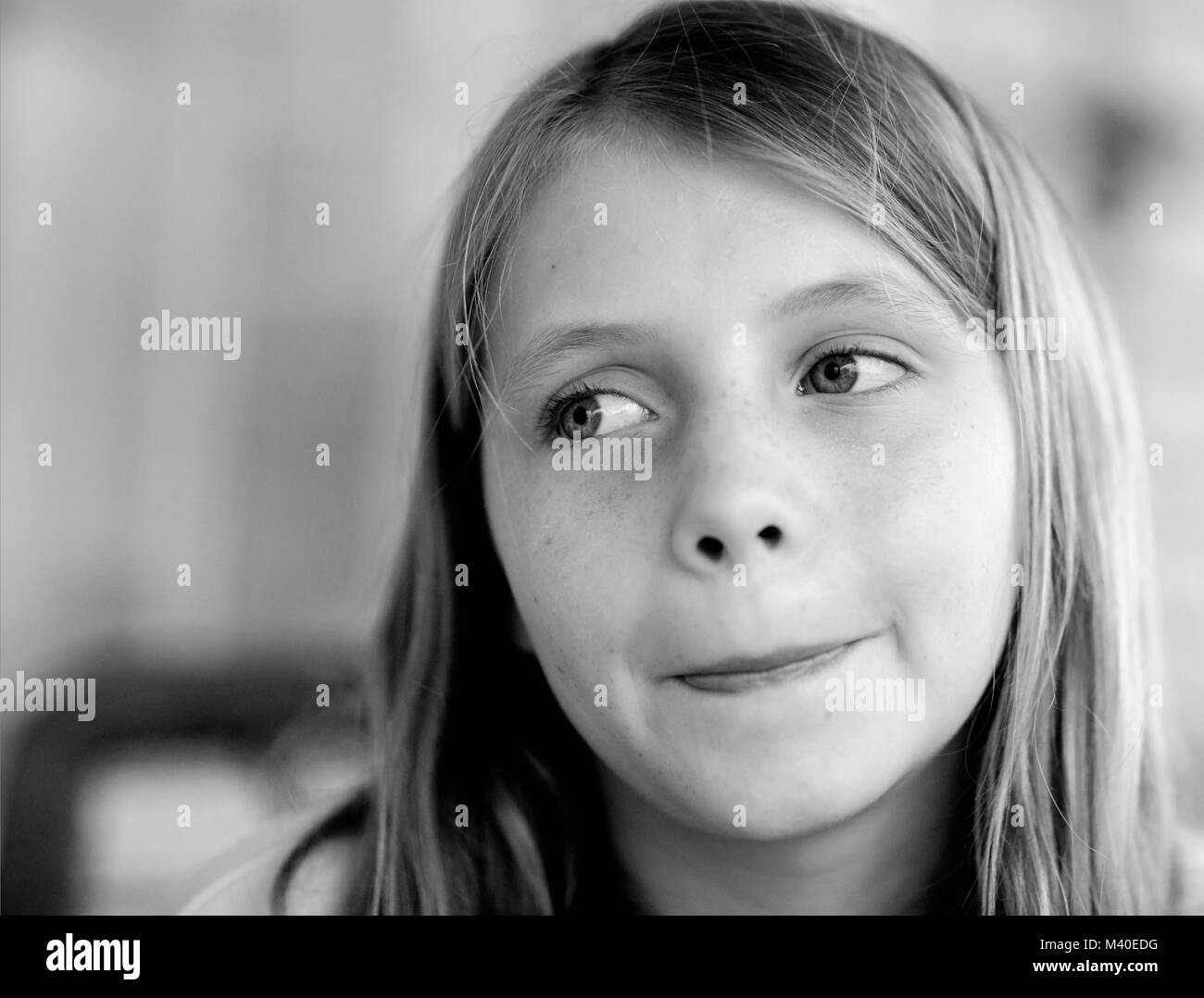 A black and white portrait of young girl with blond hair and blue eye. - Stock Image