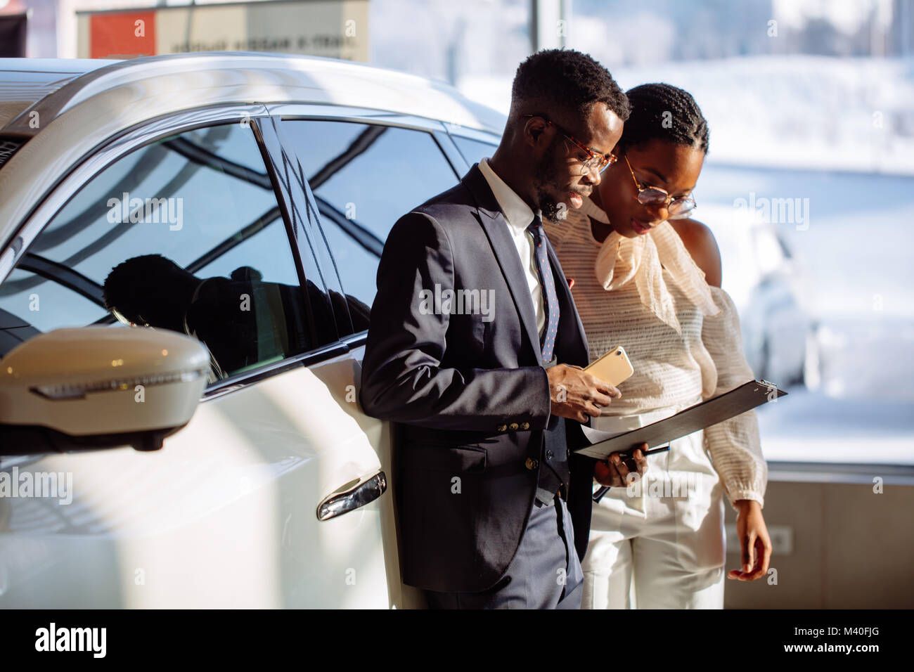 Car dealer showing vehicle to black woman - Stock Image